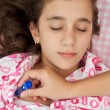 Hispanic girl sick with fever laying in her bed — Stock Photo #8822525