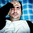 Stock Photo: Very stressed mwith headache laying in bed