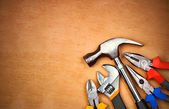 Set of manual tools over a wood panel — Stock Photo