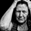 Grunge portrait of an old stressed woman — Stock Photo