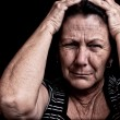 Grunge portrait of an aged woman suffering a headache — Stock Photo