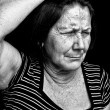 Grunge portrait of an old woman with a headache — Stock Photo