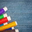 Sewing thread reels on a blue denim background — Stock Photo
