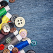 Sewing buttons and thread reels on a denim background — Stock Photo