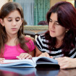 Girl reading a book with her beautiful mother — Stockfoto