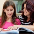 Girl reading a book with her beautiful mother — ストック写真