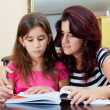 Stock Photo: Girl reading a book with her beautiful mother