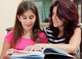 Dívka čtoucí knihu s její krásnou matkou — Stock fotografie