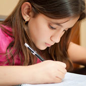 Hispanic girl working on her homework — Stock Photo