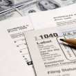 Tax Forms on top of Money - Stock Photo