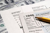 Tax Forms on top of Money — Stock Photo
