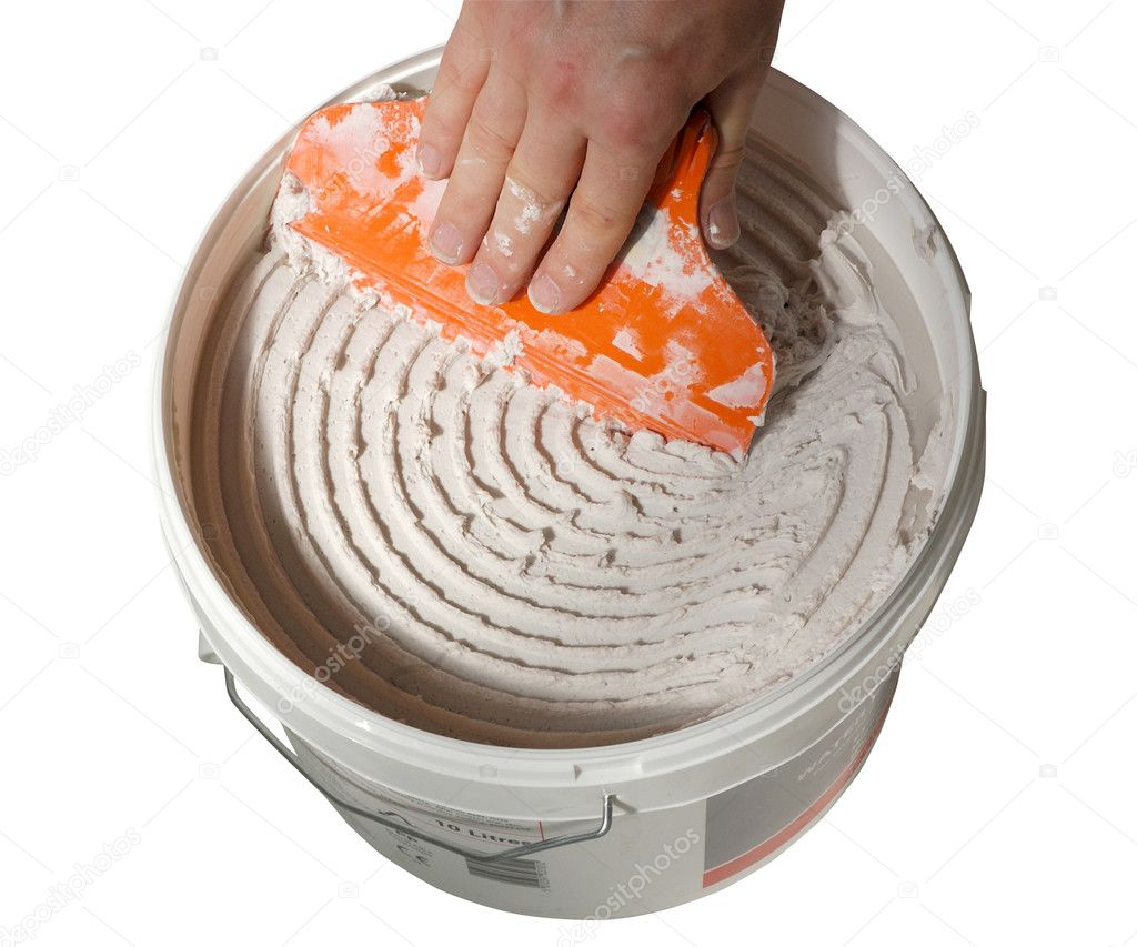 Male hand scraping adhesive out of bucket with spreader — Stock Photo #8186495