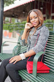 Woman sitting on a bus bench — Stock Photo