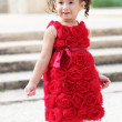 Child in a red flower dress — Stock Photo