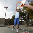 Stock Photo: Basketball player hanging from hoop