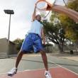 Basketball player hanging from the hoop -  