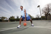 Basketball player dribbling the ball — Stock Photo