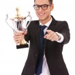 Business man holding a trophy and pointing — Stock Photo
