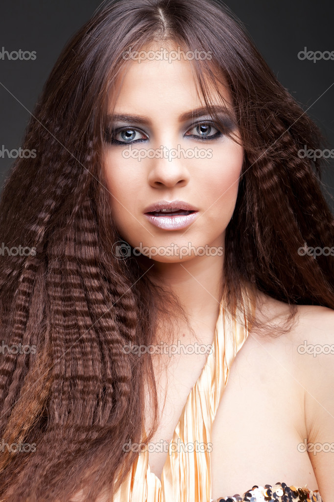 Beautiful young female face with long beauty hair on dark background — Stock Photo #10185028