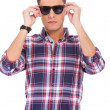 Stock Photo: Man putting sunglasses on