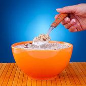 Donna con un cucchiaio con cereali — Foto Stock