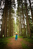 Woman walking in the fir woods — Stock Photo