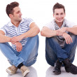Two casual men sitting on a white background — 图库照片