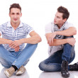 Two casual men sitting on a white background — Stock Photo
