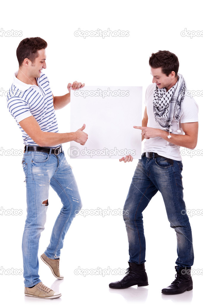Two young men holding a blank board on white background, one pointing to it and one gesturing ok with thumbs up — Stock Photo #9445386