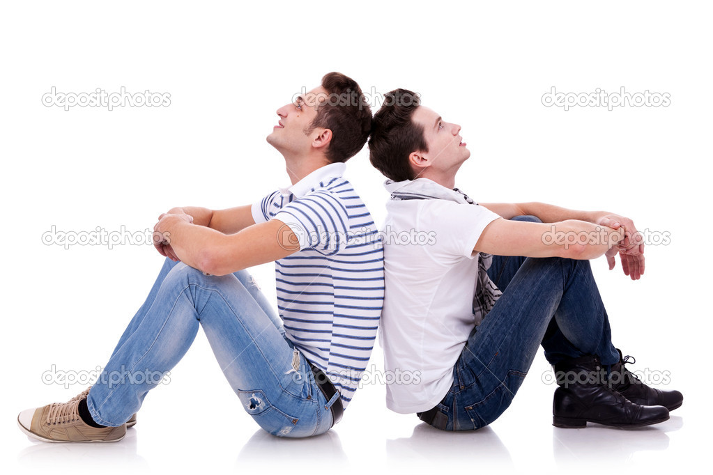 Two young casual men sitting back to back on white background and looking at something on both sides of the picture — Stock Photo #9445392