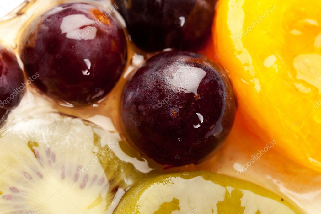 Closeup picture of a fruity cake topping made of grapes, kiwi and peaches  Stock Photo #9445499