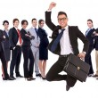 Business man holding briefcase jumping in front of his team - Stock Photo