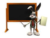 Cartoon rabbit standing in front of blank blackboard. — Stock Photo