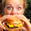 Woman eating cheeseburger - Stock Photo