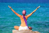 Beautiful girl meditating on the beach — Stock Photo