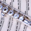 Silver flute on flute sheet music — Stock Photo