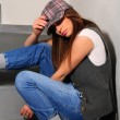 Worried young girl sitting on the stairs — Stock Photo