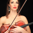 Woman holding a violin over a black background. — Stock Photo