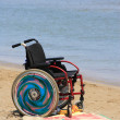 Photo of a wheelchair  on the beach - Stock Photo