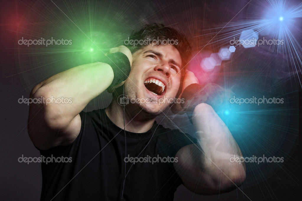 Young Man listening to music with headphones on dark background  Stock Photo #8462377