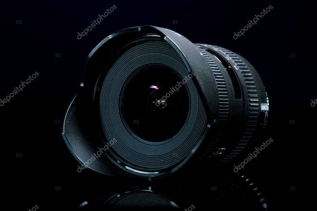 Close-up of a camera lens on a black background with reflection — Stock Photo #8464812