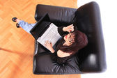 Young woman on couch and working on laptop — Foto de Stock