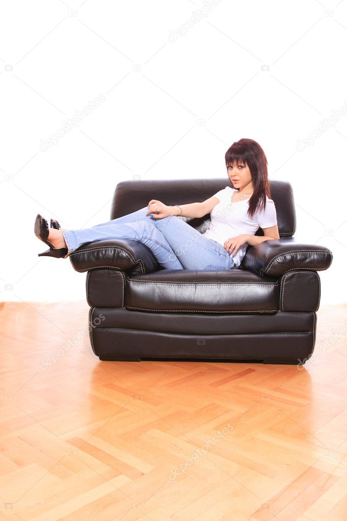 Young attractive woman relaxing on black leather sofa — Stock Photo #9038972