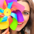 Beautiful young woman holding a multicolored pinwheel - Stock Photo