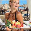 Stock Photo: Young smiling womwith fruits salad