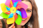 Beautiful young woman holding a multicolored pinwheel — Stock Photo