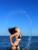 Cute girl on the beach splashing out of the water — Stock Photo
