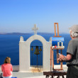 Painter artist paints a picture of Santorini - Stock Photo