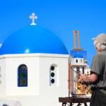 Painter artist paints a picture of Santorini — Stock Photo #9253868