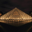 PARIS - January 8th 2012 : Closeup of Louvre Pyramid shined at dusk in Paris, France. - Stock Photo